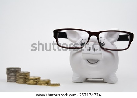 Coins lined up from short to tall stacks beside of a piggy bank with glasses - stock photo