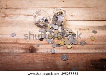 coins money in glass bottle on wooden background