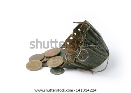 Coins next to old string purse - stock photo
