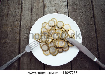 Coins on a plate with fork and knife on wooden table. Cross Processing tone colored. - stock photo