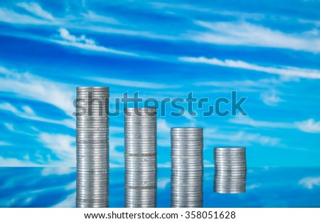 Coins on glass with blue sky background - stock photo