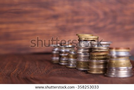 Coins on the background of mahogany. Stacks of coins of different nominal value. Concept - advertising about the bank or finances company.