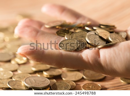 coins on the table and in hand