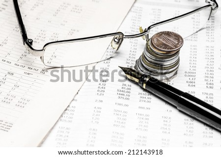 Coins, spectacles and fountain pen on a data table  - stock photo