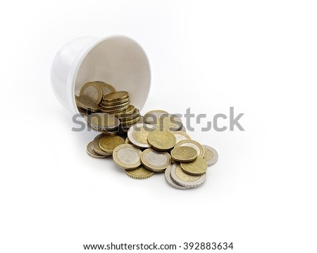 coins spilled from a white cup on a white background