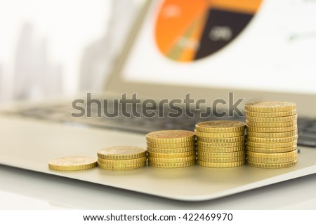 Coins stack on laptop computer in office. Concept of investment growth,investment plan, investment management, investment portfolio - stock photo