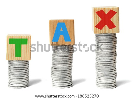 Coins stacks and wooden blocks with letters forming TAX word. - stock photo