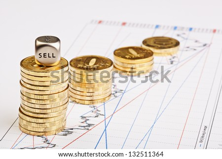 Coins stacks downtrend and the dices cube with the word SELL on financial chart. Selective focus - stock photo