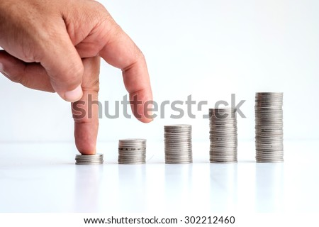 Coins stand vertically in columns ascending,revenue growth concept.