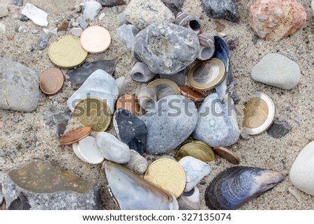 Coins, stones and shells in the sand / gold coins / at the beach