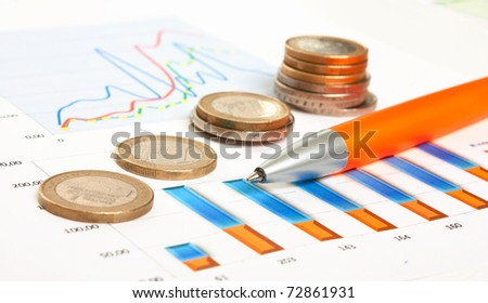 coinss and the working paper with a diagram - stock photo