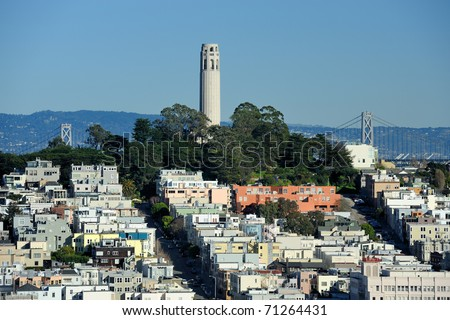Coit Tower and the Bay Bridge as viewed from the intersection of Lombard & Hyde Street in San Francisco, California - stock photo