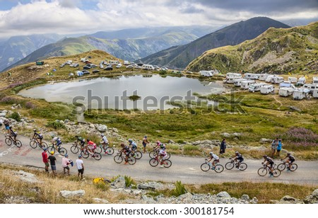COL DE LA CROIX DE FER, FRANCE - JULY 25:The peloton riding in a breathtaking cloudy natural environment at Col de la Croix de Fer in Alps during the stage 20 of Le Tour de France on 25 July 2015.  - stock photo