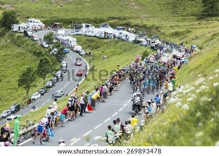 COL DE PEYRESOURDE,FRANCE-JUL 23: The peloton climbing the road to Col de Peyresourde in Pyrenees Mountains during the stage 17 of  Le Tour de France on 23 July 2014. - stock photo