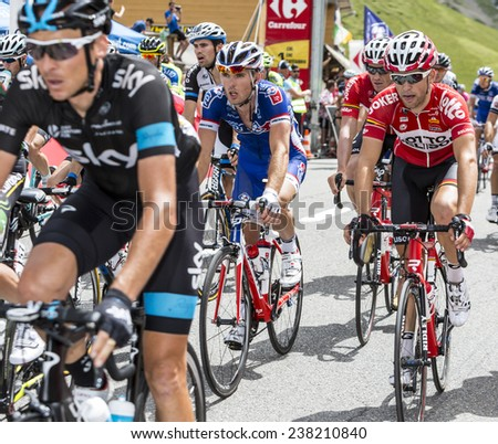 COL DU LAUTARET,FRANCE - JUL 19:Group of cyclists from various teams pedaling inside the peloton after passing the mountain pass Lautaret,during the stage 14 of Le Tour de France on July 19 2014. - stock photo