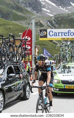 COL DU LAUTARET,FRANCE - JUL 19: The Austrian cyclist Bernhard Eisel riding near Team Sky's technical car on mountain pass Lautaret during the stage 14 of Le Tour de France on July 19 2014. - stock photo