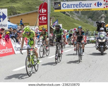 COL DU LAUTARET,FRANCE - JUL 19: The peloton arrives on Col du Lautaret in Hautes Alpes, during the stage 14 of Le Tour de France on July 19 2014. - stock photo