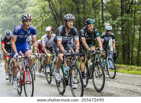 COL DU PLATZERWASEL,FRANCE - JUL 14: Group of cyclist pedaling inside the peloton while climbing the road to mountain pass Platzerwasel in Vosges Mountains, during Le Tour de France on July 14 2014 - stock photo