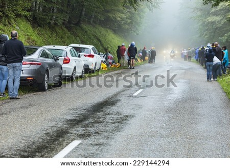 COL DU PLATZERWASEL,FRANCE - JUL 14:Spectators are waiting for the cyclists on the misty road to Col de Platzerwasel in Vosges Mountains during the stage 10 of Le Tour de France 2014. - stock photo