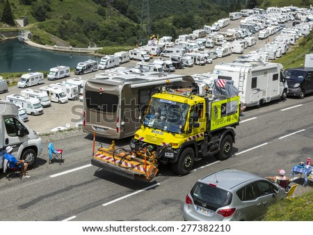 COL DU TOURMALET,FRANCE-JUL 24:Technical truck which assure the good status of the roads passing before the cyclists on the road to Col de Tourmalet in the stage 18 of Le Tour de France 2014 - stock photo
