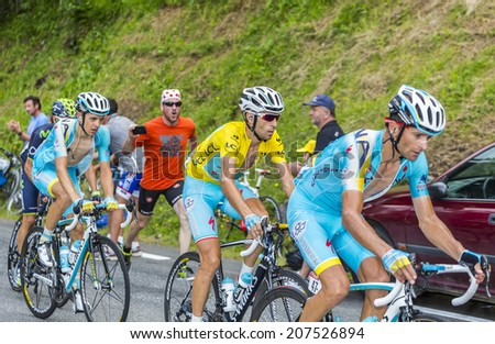 COL DU TOURMALET, FRANCE - JUL 24, 2014:Vincenzo Nibali wears the Yellow Jersey rides between his teammates on the road to Col du Tourmalet in the stage 18 of Le Tour de France on July 24, 2014. - stock photo