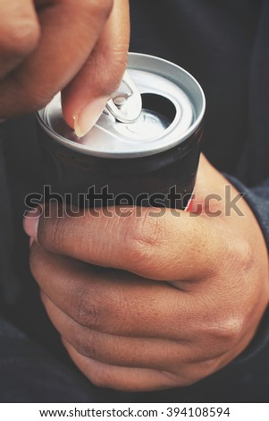 Cola can and hand