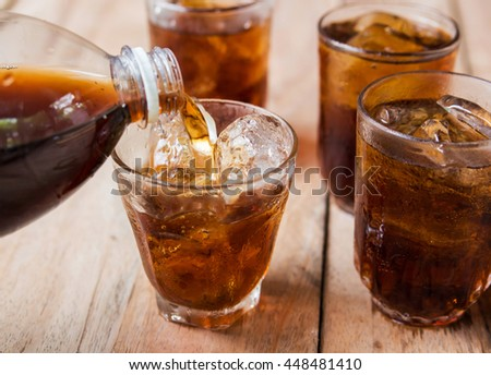 Cola drink is poured into a glass with ice.