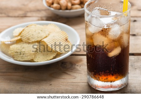 Cola glass with potato chips on a wood background. - stock photo