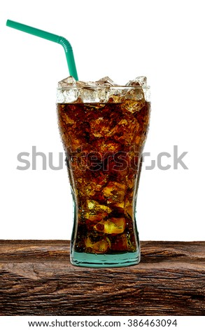 Cola in glass on wooden table with crushed ice and straw on white background - stock photo