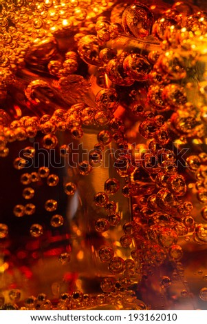 Cola in glass with ice and a bubbles of gas. Macro photo.