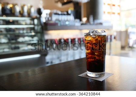 Cola on wood with restaurant background - stock photo