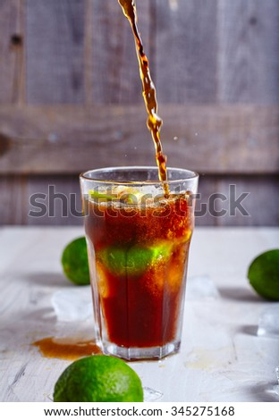 Cola that pour in glass with ice, lime and rum with limes around it. Proccess of making Cuba-Libre cocktail or Rum-Cola on wooden background - stock photo