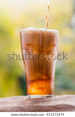 Cola water pouring into glass with ice cubes on sand, nature background - stock photo