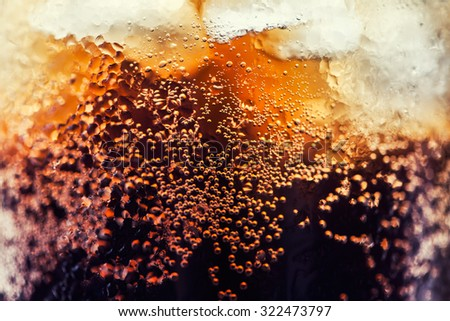 cola with ice cubes close up image
