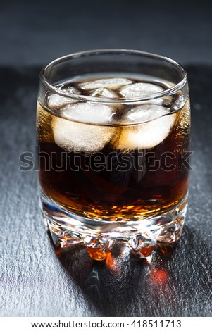 cola with ice in a glass, vertical, closeup