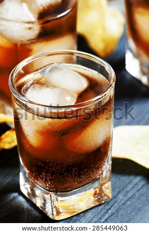 Cola with ice in glasses and potato chips on a dark background, selective focus