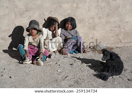 COLCHA, BOLIVIA-JAN. 12: Unidentified Bolivian children sit on the street waiting for their parents January 12,2009 in Colcha, Bolivia.Bolivian indigenous children don't have normal clothes and toys.