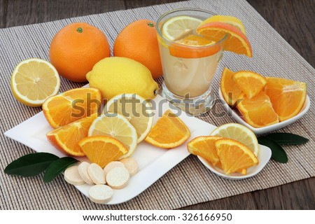 Cold and flu health remedy drink with orange and lemon fruit and vitamin c tablets on bamboo over oak background.  - stock photo