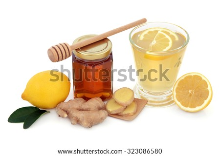 Cold and flu remedy cure with relief drink of ginger, lemon and honey over white background. - stock photo