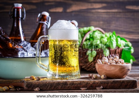 Cold and fresh beer with nuts - stock photo