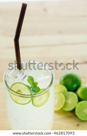 Cold and fresh drink with lime and ice on wooden table