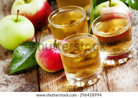 Cold apple juice and fresh apples on an old wooden table, selective focus - stock photo