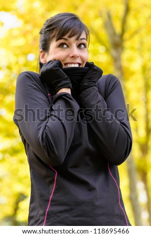 Cold autumn sport woman shivering with scarf. Caucasian brunette athlete trees on background.