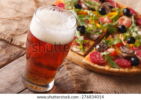 Cold beer and hot pizza with arugula on the table close-up horizontal. rustic style  - stock photo