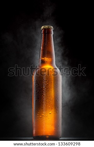 Cold beer bottle with drops, frost and vapour on black - stock photo