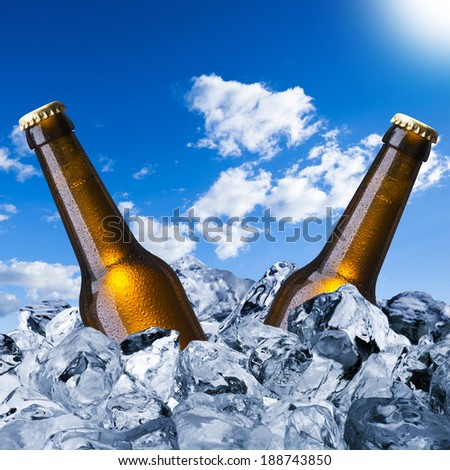 Cold beer bottles on ice cube with blue sky background - stock photo