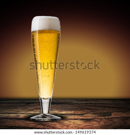Cold beer glass on wood table.