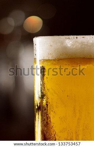 cold beer in a chilled mug served on a busy bar top