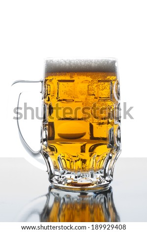 Cold beer in glass on glossy background - stock photo