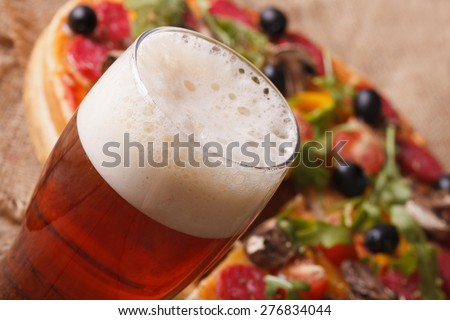Cold beer macro on a background of pizza on the table. horizontal  - stock photo